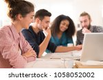 in the office. meeting around a ... | Shutterstock . vector #1058052002