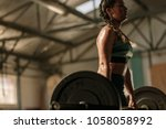 Muscular Woman In Gym Doing...