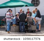 Small photo of CAMARA DE LOBOS, MADIERA - MARCH 12, 2018: Group of men watch card game in Camara de Lobos on island of Madiera