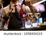 barman pours red wine | Shutterstock . vector #1058334215