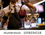 barman pours red wine | Shutterstock . vector #1058334218