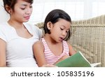 Lady teaching a young student to read. - stock photo