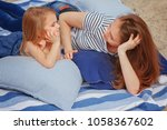 mom and daughter are lying on... | Shutterstock . vector #1058367602