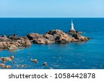 a lighthouse on the rocks.... | Shutterstock . vector #1058442878