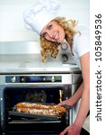 Female chef taking out baguette from oven. Bent down - stock photo