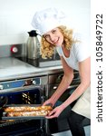 Caucasian female chef putting baguette into microwave oven - stock photo