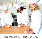 Female chefs at work in a restaurant kitchen. Kneading dough - stock photo