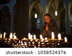 young woman praying in a church   Shutterstock . vector #1058524376