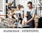 two sellers in uniform filling... | Shutterstock . vector #1058552042