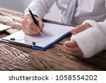 Small photo of Close-up Of A Businessperson With Broken Arm Filling Health Insurance Claim Form On Wooden Desk