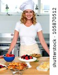 Female chef posing in uniform inside kitchen. Yummy snacks ready on the table - stock photo