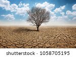 dry cracked land with dead tree ... | Shutterstock . vector #1058705195