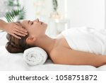 young woman enjoying massage in ... | Shutterstock . vector #1058751872