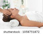 young woman enjoying massage in ... | Shutterstock . vector #1058751872