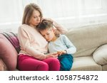 mother trying to calm her... | Shutterstock . vector #1058754872