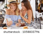 Small photo of Beautiful young women tourists spend summer holidays abroad, book tickets online with smart phone and plastic card, spends leisure time, sit together in coffee shop, drink espresso or latte.