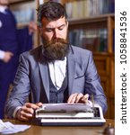 Small photo of Writers routine concept. Author types novel or poem. Writer working on new book with bookshelves on background. Man with beard and busy face sit in library and work with typewriter, close up.