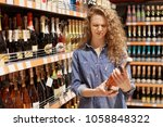 Small photo of Discontent curly young woman in denim clothes looks with unhappy expression at bottle of wine, reads information abut products, needs more sugar, dislikes drink, makes shopping in big supermarket