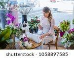florist taking orders on the... | Shutterstock . vector #1058897585