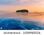 rock on frozen water lake with... | Shutterstock . vector #1058985026