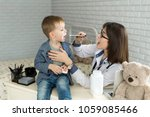 Small photo of Doctor examine child's throat. Boy at pediatrician office.