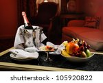 Stock photo romantic evening with bottle of champagne sweets and fruits in the hotel room 105920822