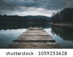 Small photo of Mole (pier) on the lake. Wooden bridge in forest in spring time with blue lake. Lake for fishing with pier. Dark and Foggy lake with hills.