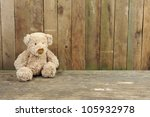 teddy bear seated against a old ... | Shutterstock . vector #105932978