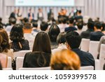 Small photo of Rear view of Audience in the conference hall or seminar meeting which have Speakers on the stage, business and education about investment concept