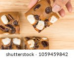 female hand picking blondies...   Shutterstock . vector #1059459842