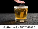 Small photo of finger hold a car key behind cup of beer concept of drunken driving