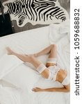 Small photo of Wedding episode. Crumpled white bedclothes. Slim, perfect and beautiful woman legs on bed