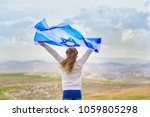 Little patriot jewish girl standing  and enjoying with the flag of Israel on blue sky background.Memorial day-Yom Hazikaron, Patriotic holiday Independence day Israel - Yom Ha