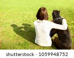 Stock photo girl in the park sits with her big dog cane corso rear view 1059948752