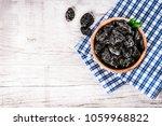 fresh dried prunes in wood bowl ... | Shutterstock . vector #1059968822