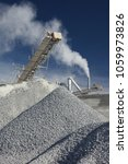 Small photo of Rock stone crushing machine against a blue sky, closeup. Mining industry. Quarry and mining equipment.
