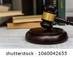 judge gavel beside pile of... | Shutterstock . vector #1060042655