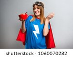 pretty superhero girl eating... | Shutterstock . vector #1060070282