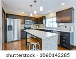Stock photo spacious kitchen with open floor plan features chocolate brown cabinets and an island with granite 1060142285
