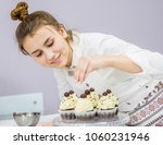 happy girl decorates cupcakes... | Shutterstock . vector #1060231946