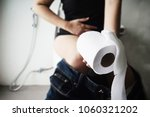 woman sitting on toilet bowl... | Shutterstock . vector #1060321202