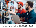 Small photo of Two salesmen in red shirt and baseball cap and blue robe are checking tooks inventory with laptop in power tools store.