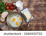 fried eggs in a frying pan with ... | Shutterstock . vector #1060433732