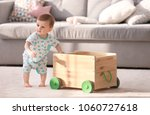 Stock photo cute baby holding on to wooden cart in living room learning to walk 1060727618