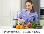 woman in kitchen chopping fruit ... | Shutterstock . vector #1060741232