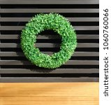 Small photo of Boxwood wreath on exterior wall with blond wood accent below.