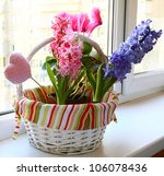spring flowers in a small basket on a balcony - stock photo