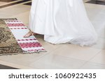 bride putting leg on... | Shutterstock . vector #1060922435