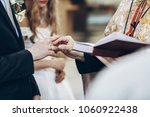 priest putting on wedding rings ... | Shutterstock . vector #1060922438
