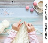 Small photo of Knitting with knitting needles. White knitted fabric. Coffee Americano. Light aged background.
